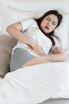 Femme avec maux de ventre sur le lit
