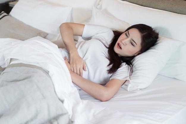 Femme avec maux de ventre sur un lit
