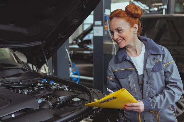 Femme mécanicien travaillant à la station service de voiture