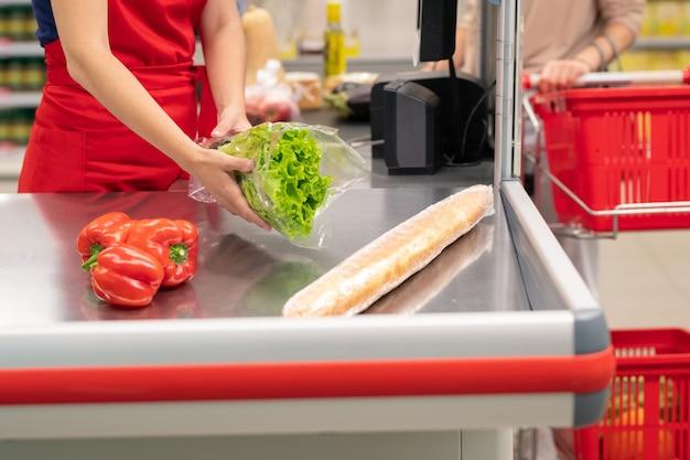 Femme méconnaissable achetant des aliments dans un supermarché moderne, le caissier les bip