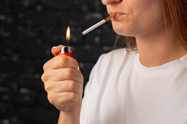 Femme méconnaissable allume une cigarette avec un allume-feu