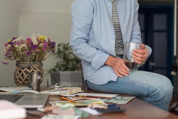 Femme méconnaissable assise sur un bureau en désordre