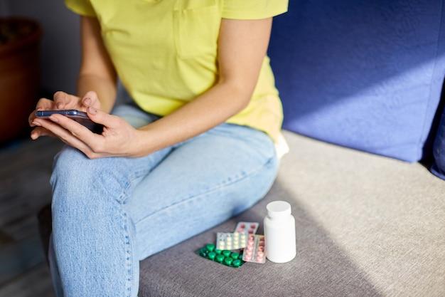 Femme méconnaissable assise sur un canapé avec blister de pilules à l'aide de la pharmacie en ligne, acheter une pharmacie sur internet