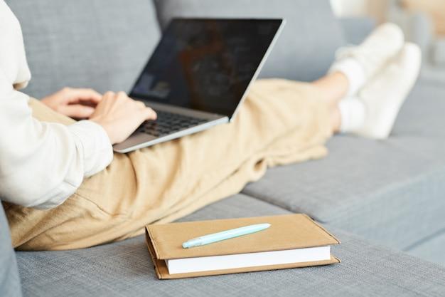 Femme méconnaissable assise détendue sur un canapé à la maison travaillant sur son ordinateur portable, prise de vue horizontale