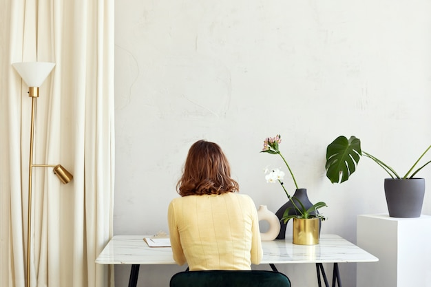 Femme méconnaissable assise à table avec des fleurs à la maison