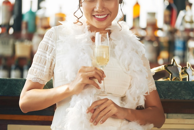 Femme méconnaissable avec boa à plumes blanches, tenant un verre de champagne au bar
