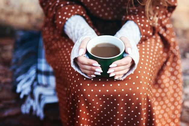 Femme méconnaissable buvant du café dans la forêt