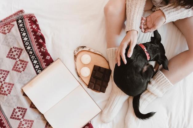 Femme méconnaissable caresser chien près de livre et dessert