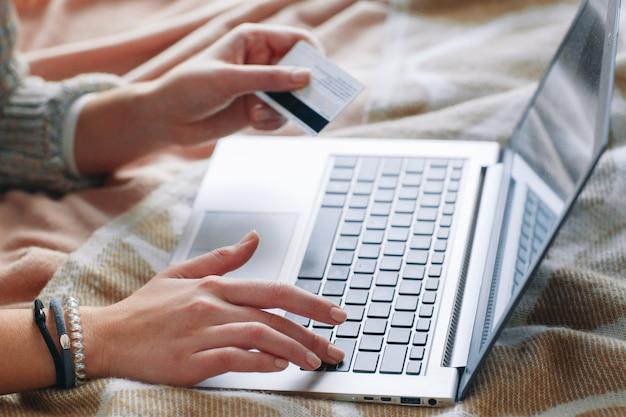 Femme méconnaissable avec carte de crédit sur ordinateur portable