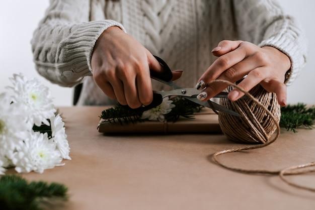 Une femme méconnaissable avec des ciseaux a coupé une corde naturelle pour emballer ses cadeaux.
