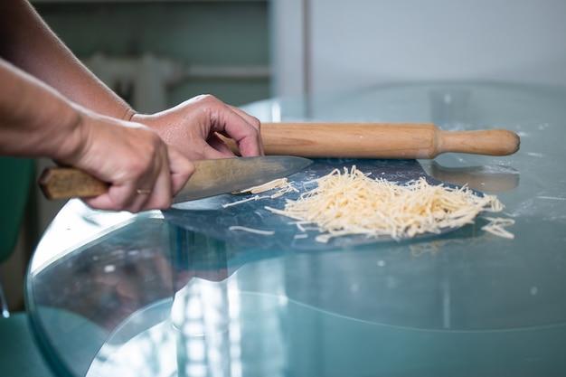 Une femme méconnaissable coupe les mains des femmes de nouilles en gros plan