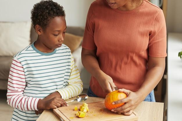 Femme méconnaissable debout au comptoir de la cuisine montrant à son fils comment sculpter la citrouille pour halloween