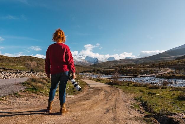 Femme méconnaissable debout sur la route non goudronnée au bord de la rivière avec un appareil photo professionnel avec des montagnes enneigées en arrière-plan sous un ciel bleu