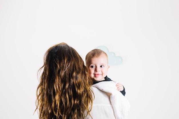 Femme méconnaissable étreindre bébé souriant