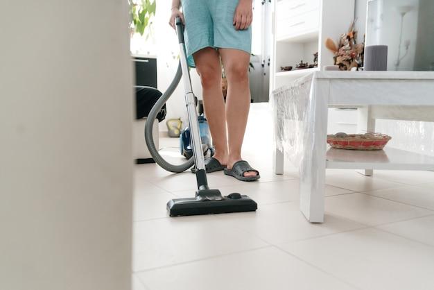 Femme méconnaissable nettoyant la maison avec l'aspirateur.