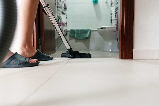 Femme méconnaissable nettoyant la salle de bain avec aspirateur.