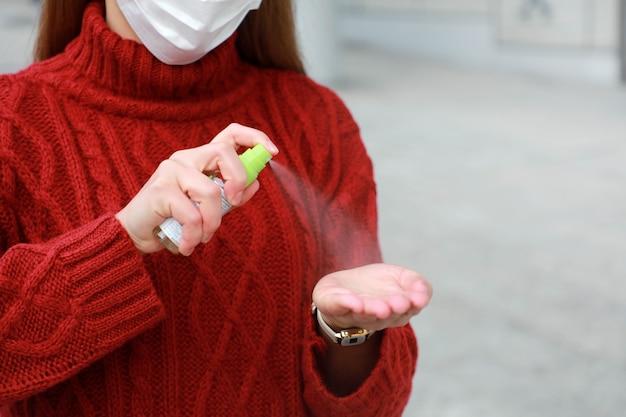 Femme méconnaissable portant un masque de protection pulvérisant un désinfectant pour les mains en spray d'alcool dans la rue de la ville