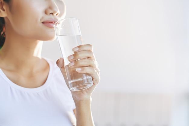 Femme méconnaissable portant un verre d'eau à la bouche