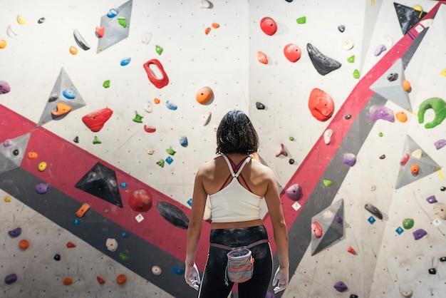 Femme méconnaissable prête à pratiquer l'escalade sur mur artificiel à l'intérieur. mode de vie actif et concept de bloc.