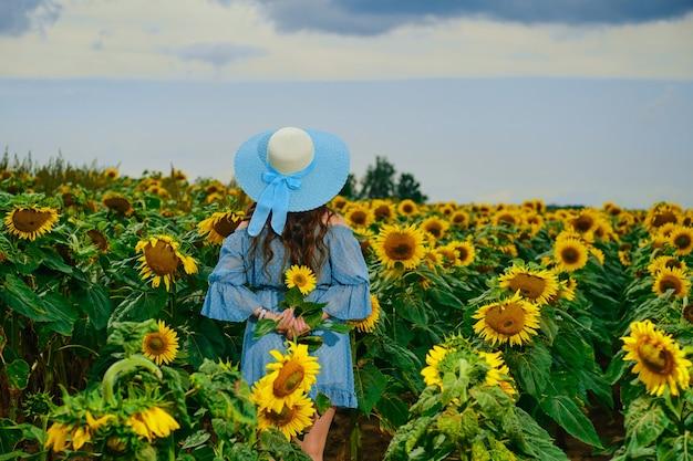 Une femme méconnaissable se tient dans un champ de tournesol avec ses mains derrière son dos et tient du tournesol