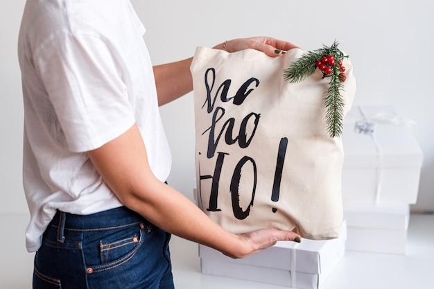 Femme méconnaissable tenant un cadeau de noël dans un sac en tissu