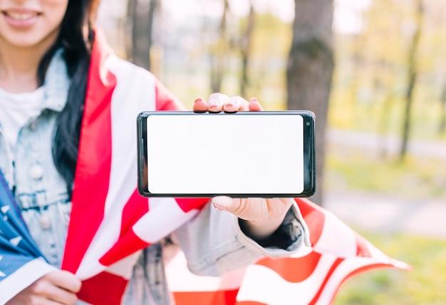 Femme méconnaissable tenant le drapeau américain et téléphone mobile