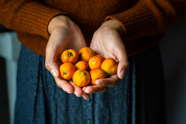 Femme méconnaissable tenant des fruits tejocotes
