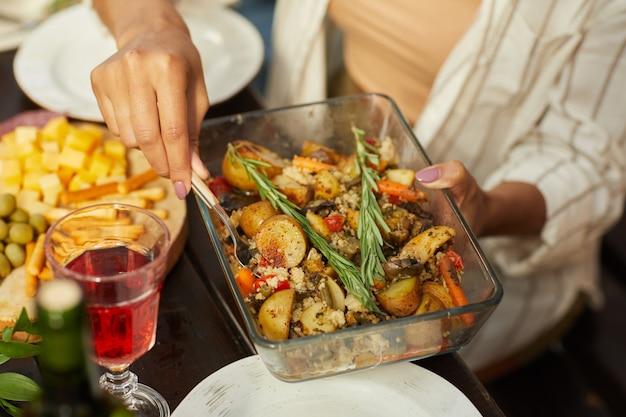 Femme méconnaissable tenant un plat avec des pommes de terre rôties dorées tout en appréciant le dîner avec des amis et la famille à l'extérieur