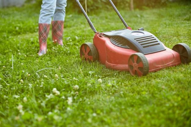 Une femme méconnaissable tond la pelouse avec une tondeuse à gazon dans le jardin de la maison, une jardinière travaillant, un beau paysage d'été, la lumière du soleil, un superbe design à toutes fins utiles, un concept de jardinage