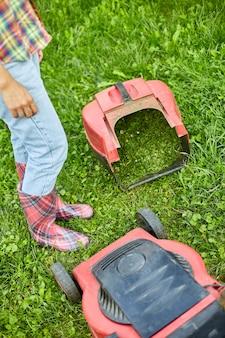 Femme méconnaissable avec une tondeuse à gazon dans le jardin de la maison, jardinière travaillant, beau paysage d'été, lumière du soleil, superbe design pour tous les usages, concept de jardinage