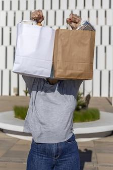 Femme méconnaissable transportant du papier recyclable sac de nourriture à emporter