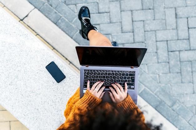 Femme méconnaissable utilisant un ordinateur portable dans la rue. concept de femme d'affaires