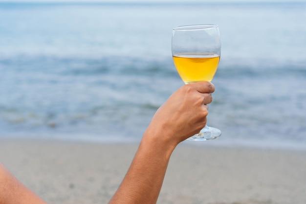 Femme méconnaissable avec un verre de vin sur la plage