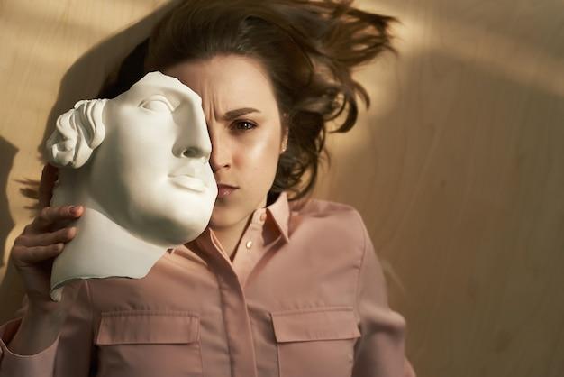 Une femme mécontente est allongée sur le sol, fronce les sourcils, couvre le visage détruit une partie de la tête en plâtre blanc