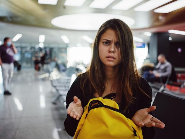 Une femme mécontente lève ses mains à l'aéroport en attente d'un sac à dos doré de vol