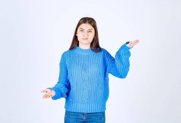 Femme mécontente en pull bleu debout sur blanc.