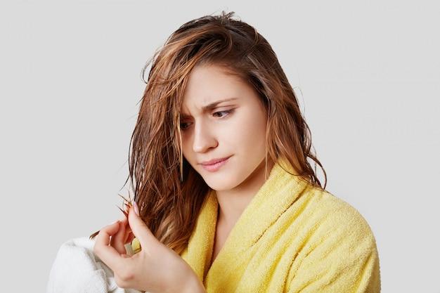 Une femme mécontente regarde les cheveux humides et raides, insatisfaite du shampooing, a les pointes fourchues, porte un peignoir