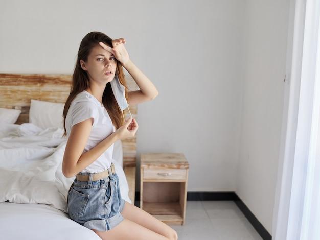 Une femme mécontente se touche la tête avec sa main et s'assoit sur le lit à l'intérieur du coronavirus de quarantaine