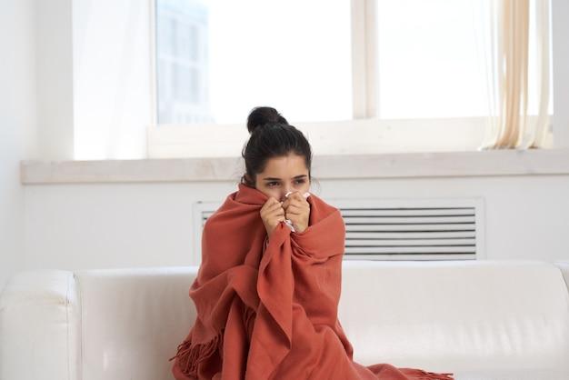Femme mécontente et se trouve à la maison sur le canapé pour le rhume