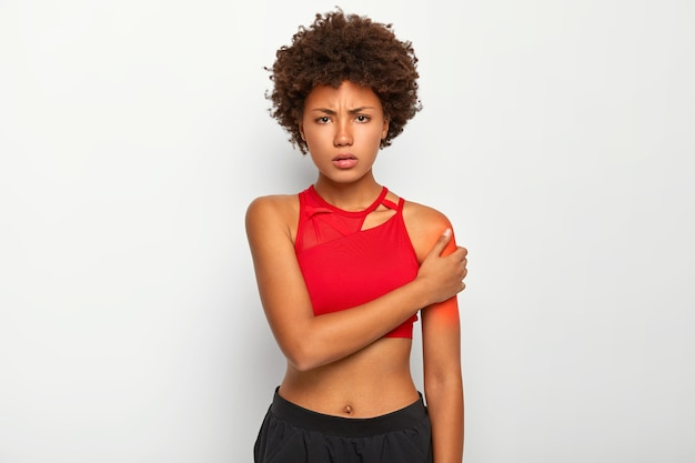 Femme mécontente à la silhouette mince, vêtue d'un haut et d'un pantalon rouges, touche l'épaule, souffre de douleur, se blesse