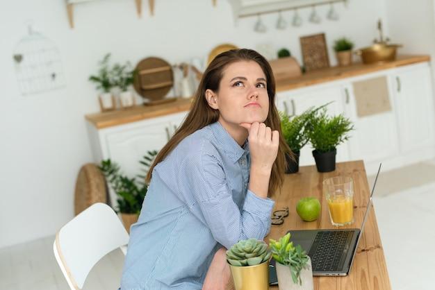 Une femme mécontente et songeuse pense à résoudre un problème tout en travaillant à distance à la maison. difficultés en télétravail ou en apprentissage.