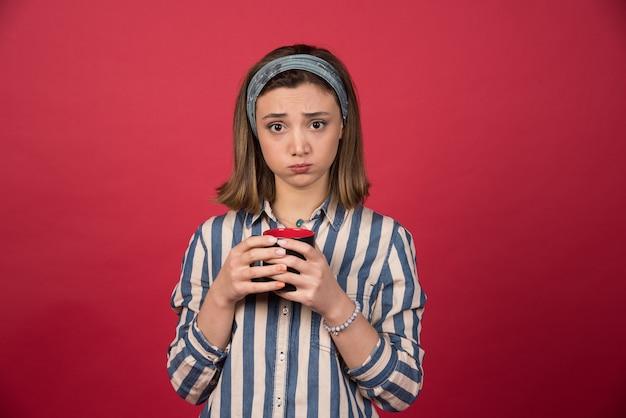 Femme mécontente tenant une tasse de café sur un mur rouge