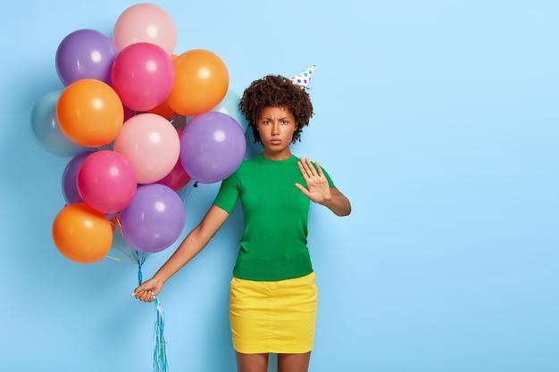 Femme mécontente tient des ballons multicolores tout en posant avec un chapeau d'anniversaire