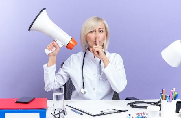 Femme médecin adulte confiante en robe médicale avec stéthoscope assise au bureau avec des outils de bureau tenant un haut-parleur et faisant un geste de silence isolé sur un mur violet avec espace de copie