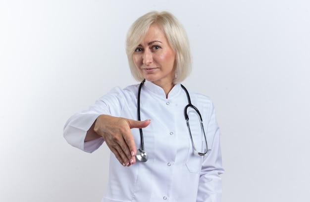 Femme médecin adulte heureuse en robe médicale avec stéthoscope tendant la main isolée sur un mur blanc avec espace de copie