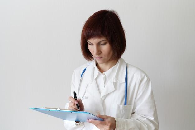 Femme médecin adulte se dresse sur blanc
