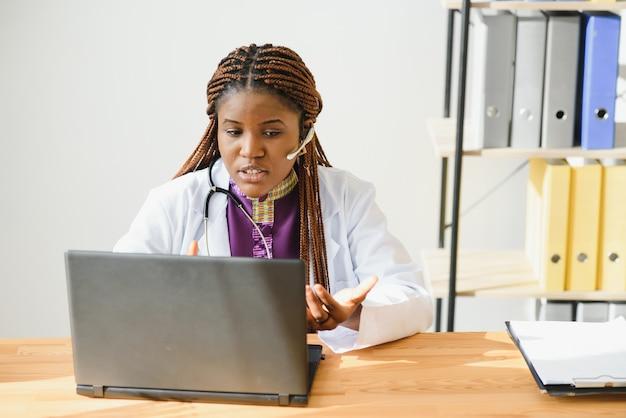 Une femme médecin africaine consultant un patient effectue un appel vidéo webcam en ligne sur ordinateur portable.