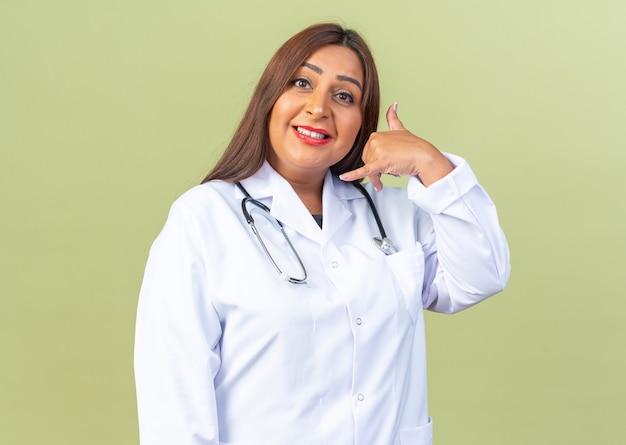 Femme médecin d'âge moyen en blouse blanche avec stéthoscope à l'air heureux et positif en me faisant appeler un geste souriant joyeusement