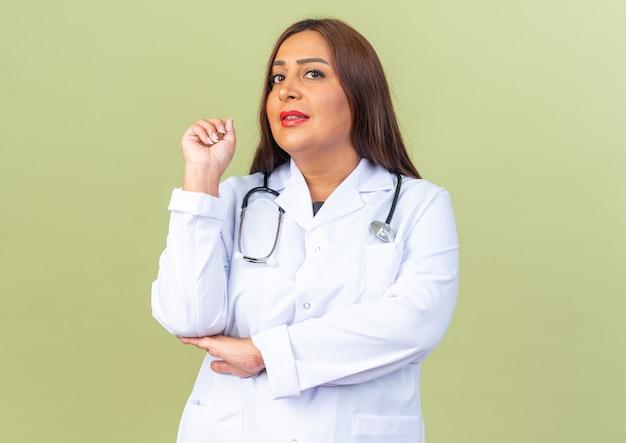 Femme médecin d'âge moyen en blouse blanche avec stéthoscope avec expression sceptique pointant vers l'arrière debout sur un mur vert