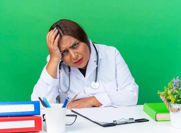 Femme médecin d'âge moyen en blouse blanche avec stéthoscope fatiguée et ennuyée assise à la table sur un mur vert